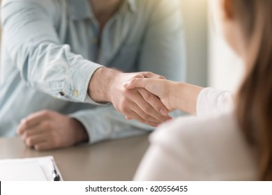 Businessman shaking female hand above the table. Business agreement and partnership concept. Partners closing a deal, view over the shoulder. Formal greeting  gesture, effective negotiations