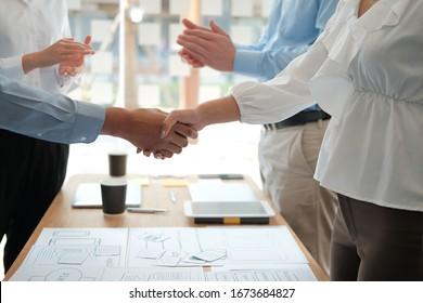 Geschäftsmann, der nach dem UI UX-Designer-Treffen mit Geschäftsfrau die Hände schüttelt. Geschäftsleute, die sich von Hand bewegen. Grußgeschäft, Teamwork-Partnerschaftskonzept.