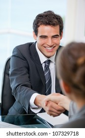 Businessman shaking hands with a client while smiling in an office
