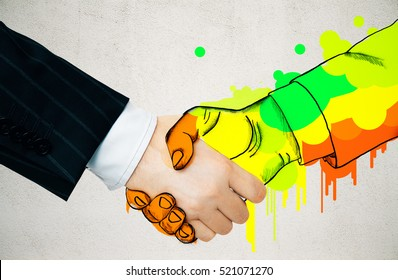 Businessman shaking hands with colorful drawn colleague on concrete background. Creative business concept