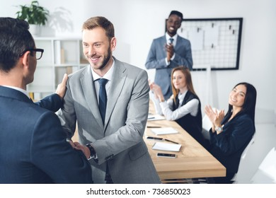 businessman shaking hands in conference hall with partners sitting at table