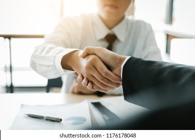 Businessman shaking hands with customer in office.