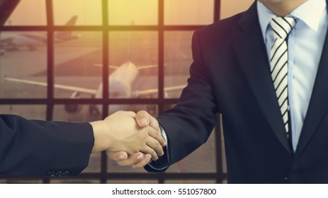 businessman shaking hands each other at airport, concept in success, finance and cooperation with  foreigner