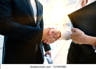 businessman shaking hands with a girl business partner