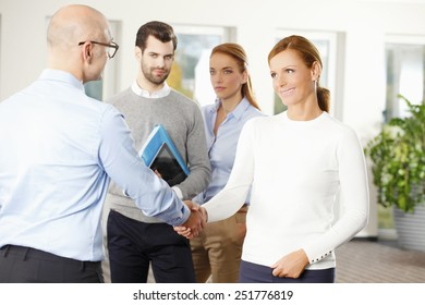 Businessman shaking hands at meeting.