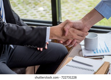 Businessman shaking hands in office.