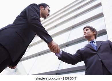 Businessman shaking hands outside modern office building