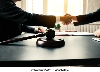 Businessman shaking hands to seal a deal with his partner lawyers or attorneys discussing a contract agreement and lawsuit.