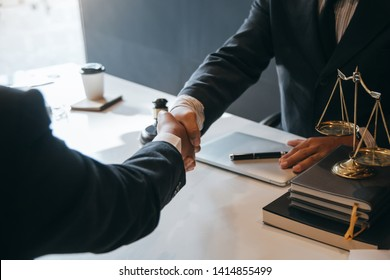 Businessman shaking hands to seal a deal with his partner lawyers or attorneys discussing a contract agreement.