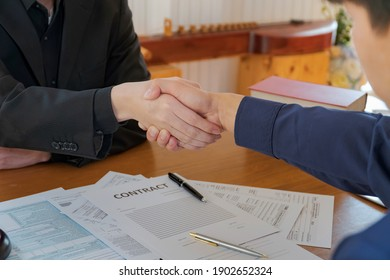 Businessman shaking hands to seal a deal with his partner lawyers or attorneys after discussing a contract agreement and signing in contract