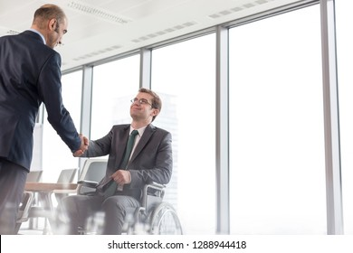 Businessman shaking hands with smiling disabled colleague in boardroom during meeting at office