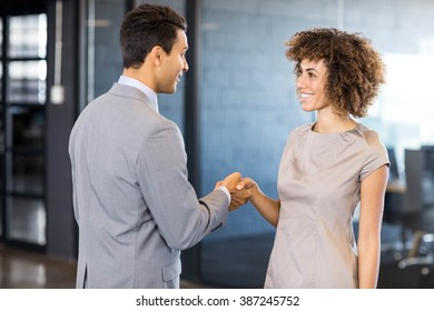 Businessman shaking hands young woman in office - Shutterstock ID 387245752