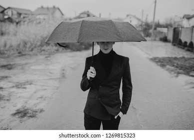 Businessman sheltering from the rain under an umbrella looking up at the change in the weather. Financial safety. Raining day in city park view, risk and crisis concept.