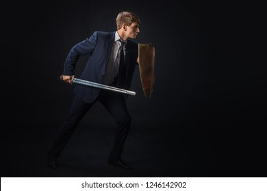 Businessman with shield and sword in the fighting rack, free space on the right. Anti-virus and information protection concept, gdpr
