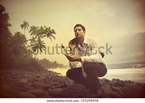 Businessman Shipwrecked on a desert island with message in a bottle.