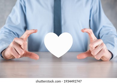 Businessman in shirt holding heart icon symbol .
