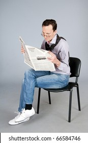 Businessman in shirt and scarf sitting on a chair and reading newspaper.