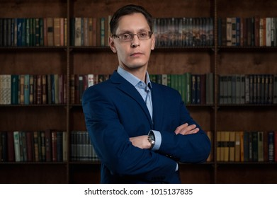 Businessman in shirt and suit against the background of books. Business portrait. Business style.