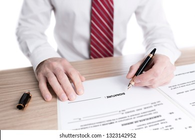 businessman in shirt and tie signing a paper contract with a fountain pen on a desk