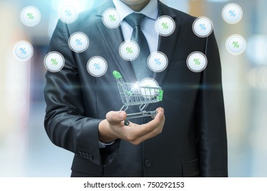 Businessman with shopping cart from which fly the interest on blurred background.
