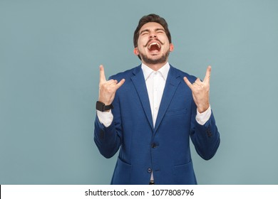 Businessman shout and showing rock and roll sign. Business people concept, richly and success. Indoor, studio shot on light blue background
