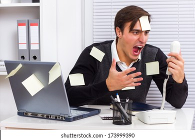 Businessman shouting on telephone at his office,Frustrated businessman