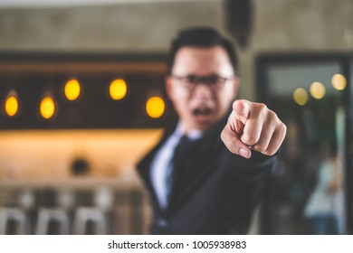 businessman shouting and pointing finger at you because he is very angry from Sales reports and financial reports decreased.