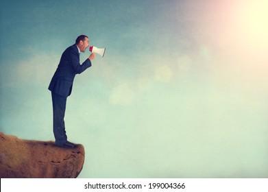 businessman shouting through a megaphone from a mountain edge