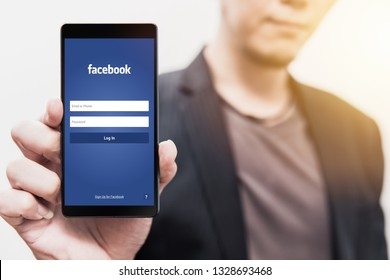 businessman show Facebook login page on his smartphone for using phone social app for business. 3 August 2018,Bangkok, Thailand.