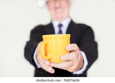 Businessman showing coffee mug to camera