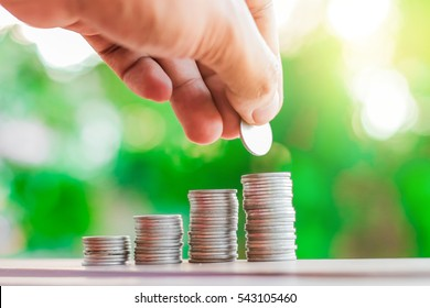Businessman showing collect many coins with fresh nature blurred background and sunlight.