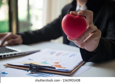 Businessman showing compassion holding red heart onto his chest, service mind business concept