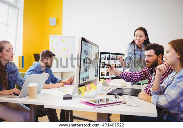 Businessman showing computer screen to coworkers in creative office