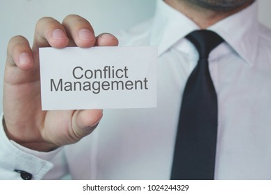 Businessman showing Conflict Management word on business card.