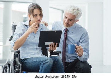 Businessman showing a document on a clipboard to a young woman in wheelchair, assistance and help concept
