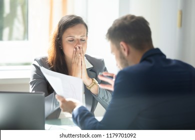 Businessman Showing Document To Stressed Young Female Employee