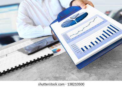 Businessman Showing Financial Charts on the Clipboard in the Office