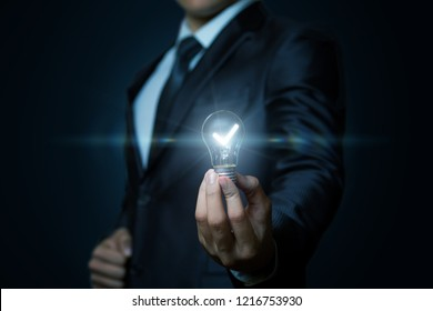 A businessman is showing a glowing lightbulb in his hand at the dark background. The concept is the creative idea.