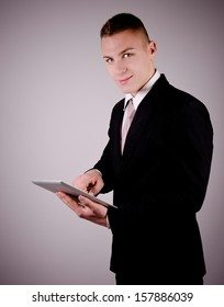 Businessman showing his tablet in front of gradient background.