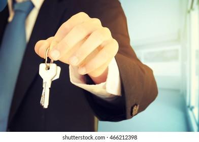 businessman showing key of building as development concept