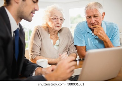 Businessman showing laptop to senior couple at home