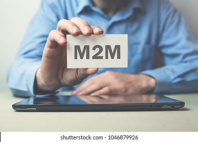 Businessman showing M2M word on business card.