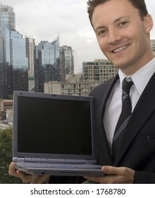 A businessman is showing off a laptop with a blank screen.