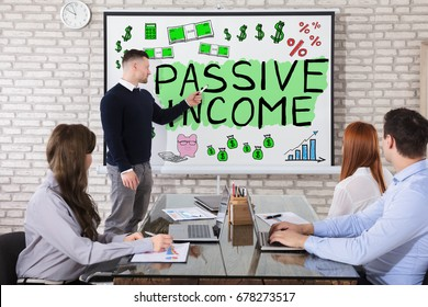 Businessman Showing Passive Income Concept On Whiteboard To His Colleague In Office