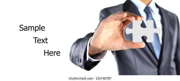 Businessman showing a piece of puzzle. Shot in studio isolated on white