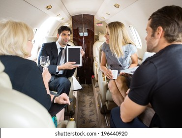 Businessman showing project on digital tablet to partners in private jet