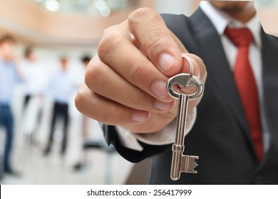 businessman showing the silver key to success
