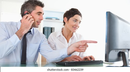 Businessman showing something to his coworker on a computer in an office