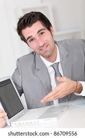 Businessman showing something on laptop computer