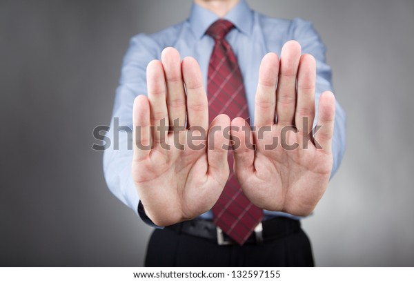 Businessman showing stop hand sign. Neutral background